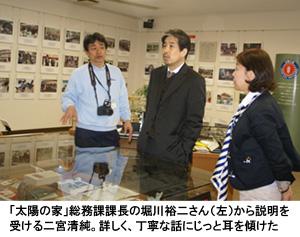 写真:「太陽の家」総務課課長の堀川裕二さん(左)から説明を受ける二宮清純。詳しく、丁寧な話にじっと耳を傾けた