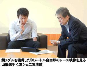 銅メダルを獲得した50メートル自由形のレース映像を見る山田選手<左>と二宮清純