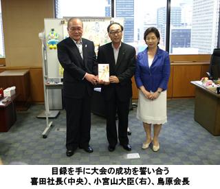 写真:目録を手に大会の成功を誓い合う喜田社長(中央)、小宮山大臣(右)、鳥原会長