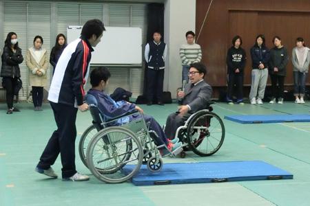 講師の指導で車椅子を持ち上げる。「コミュニケーションとおもてなし(障がいのある方への接し方)車いす編」実技講習