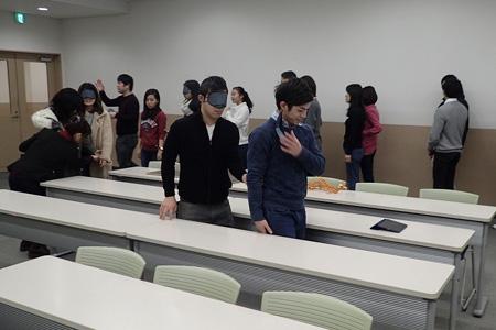 視覚障害者誘導の講習を受ける学生たち。「コミュニケーションとおもてなし(障がいのある方への接し方)視覚障害者編」実技講習