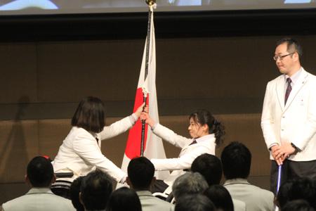 平昌冬季パラリンピック日本選手団大日方邦子団長(左)から、団旗を受け取る旗手の村岡桃佳(中央)