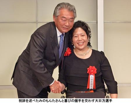 写真:祝辞を述べたみのもんたさんと喜びの握手を交わす大日方選手
